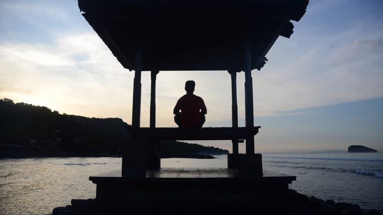 Man sitting in a pagoda for morning meditation