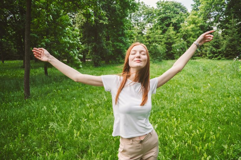 Happy woman practising a self-love dance outdoors