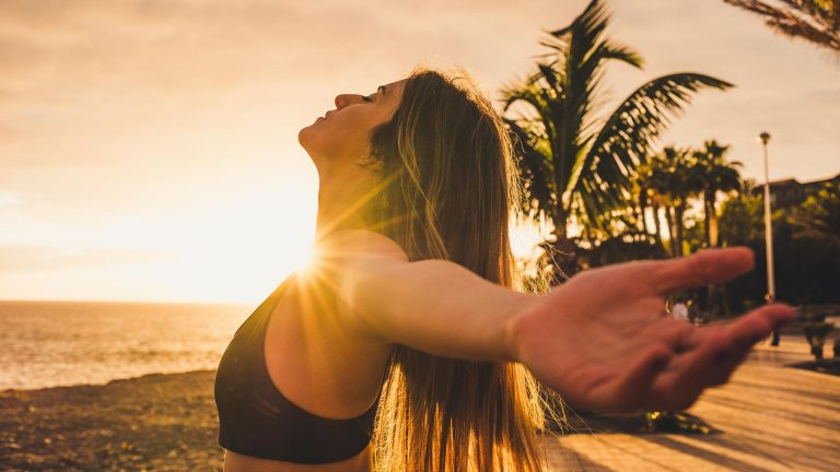 Woman practising breathing exercises on the beach